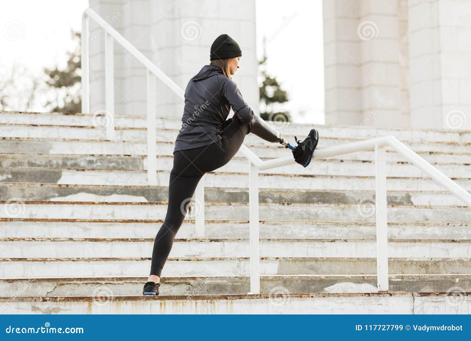 Immagine della ragazza corrente disabile in abiti sportivi, nell addestramento e nello stret