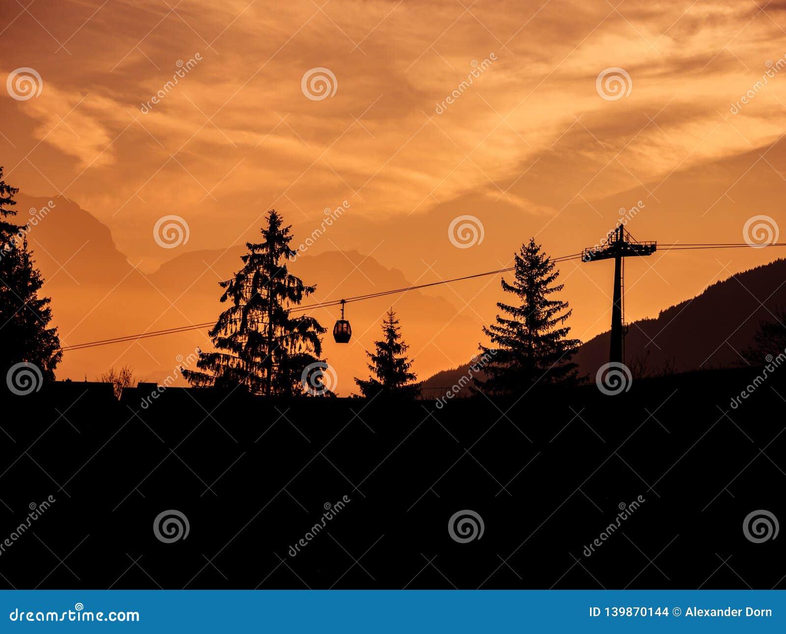 Immagine delle siluette dell ascensore e degli alberi di sci durante l alba nel primo mattino