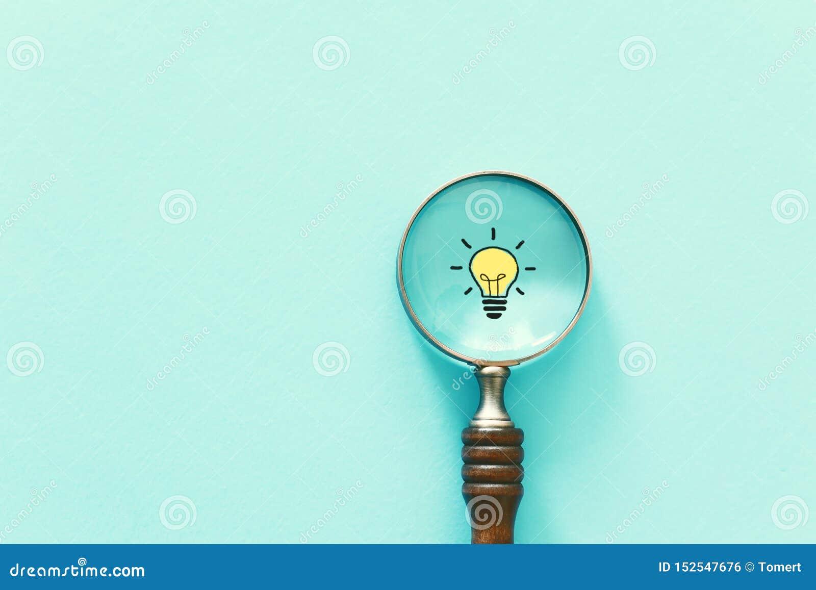 Immagine di concetto di affari Lente d ingrandimento e lampada Trovando la migliori idea ed ispirazione tra l altro