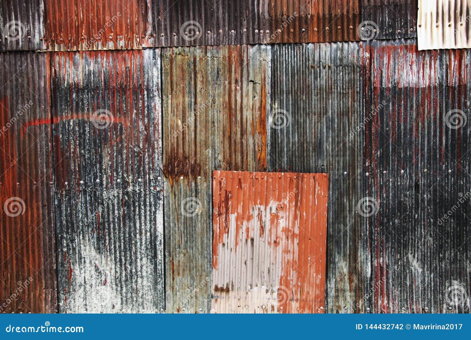 Immagine di sfondo degli strati ondulati arrugginiti del ferro del metallo rossi e dei colori blu