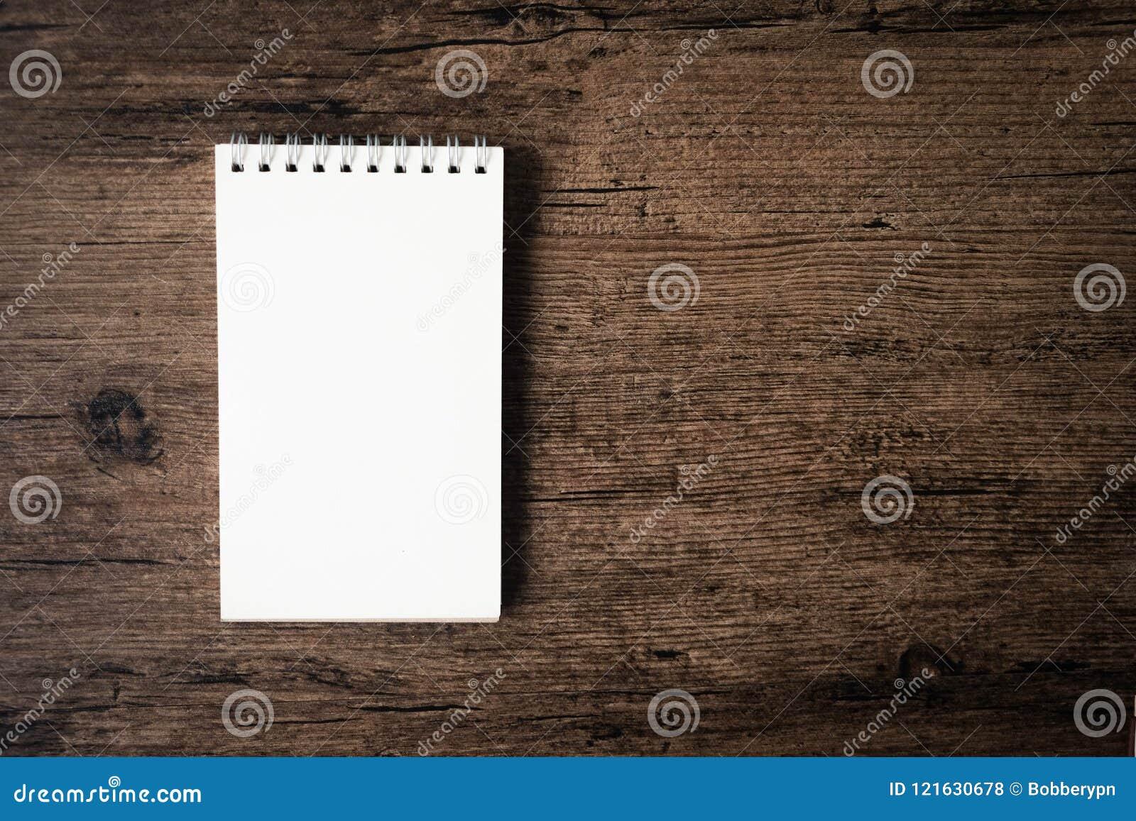 Immagine di vista superiore del taccuino aperto con la pagina in bianco sui tum di legno
