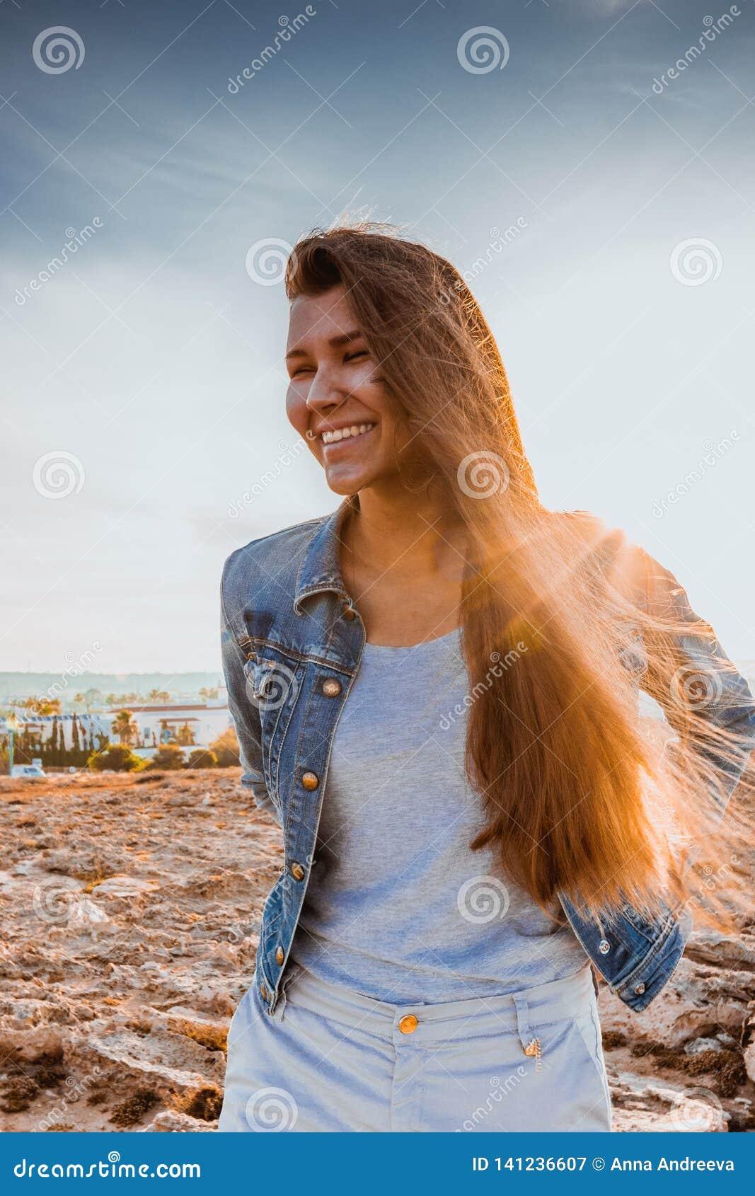 Immagine luminosa della donna di risata sulla spiaggia luce solare della lampadina nel backgroiund Bello giovane modello femminil