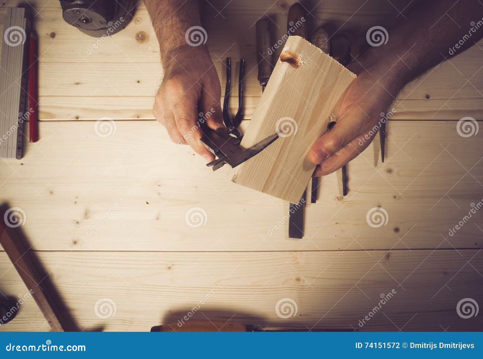 Immagine potata del legno di misurazione del carpentiere senior in officina