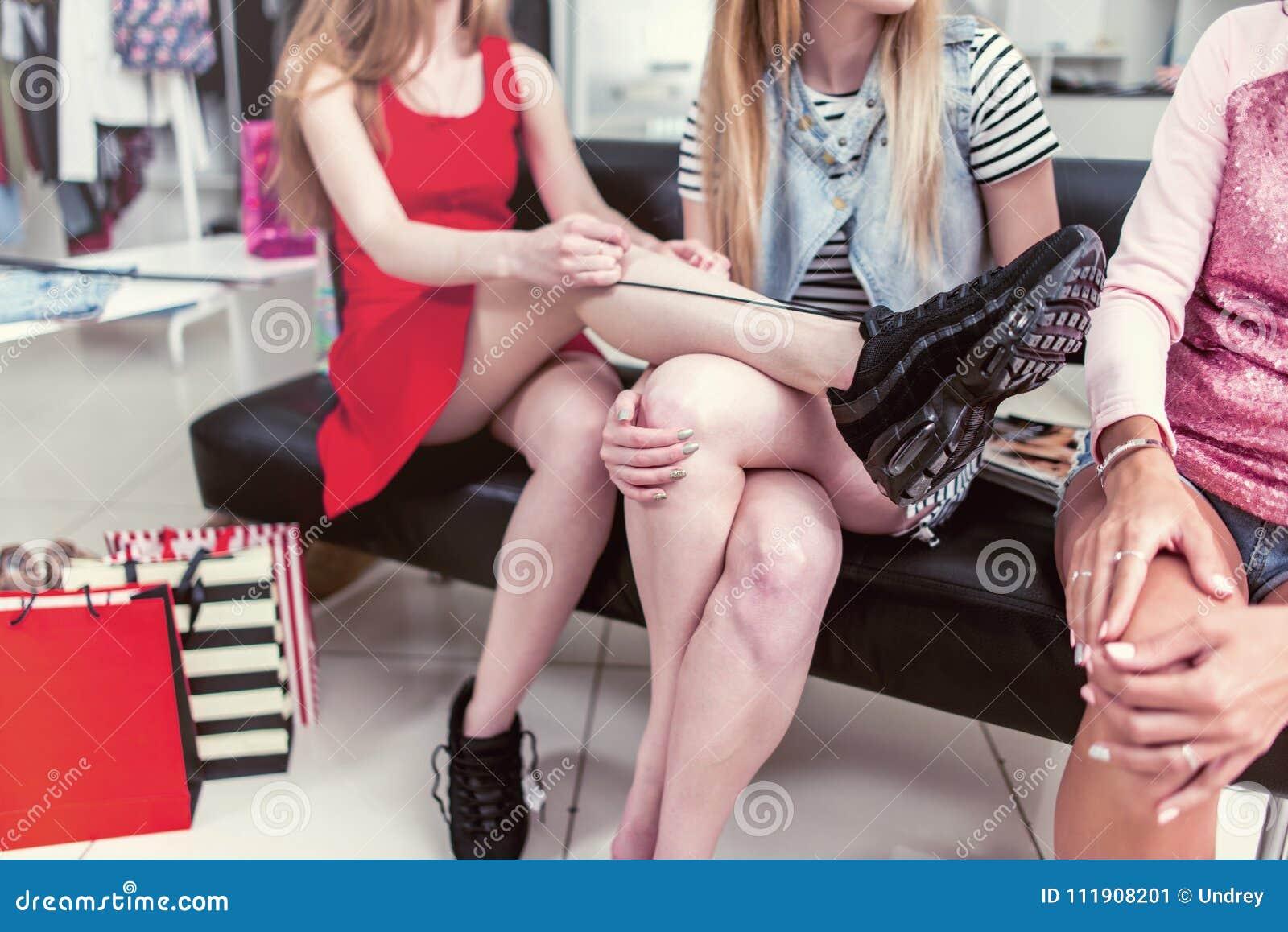 Immagine potata delle ragazze teenager che si siedono sul banco che si rilassa dopo la compera nel negozio di vestiti Giovane leg