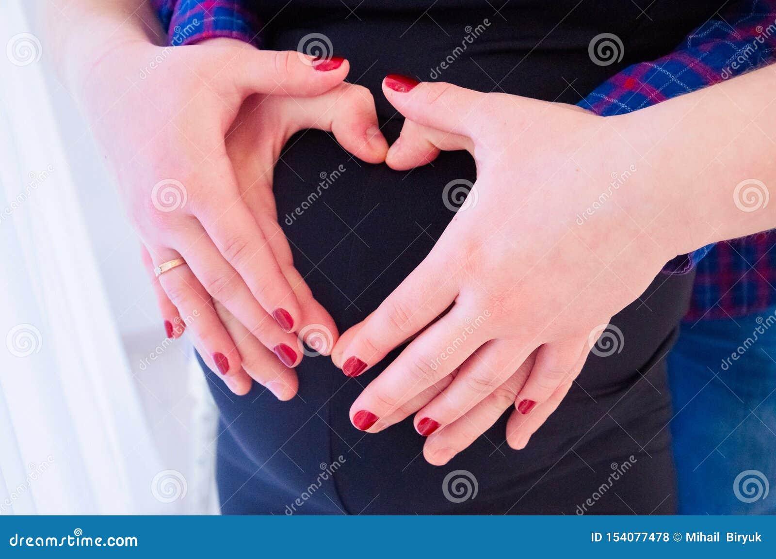 Immagine potata di bella donna incinta e suo del marito bello che abbracciano la pancia