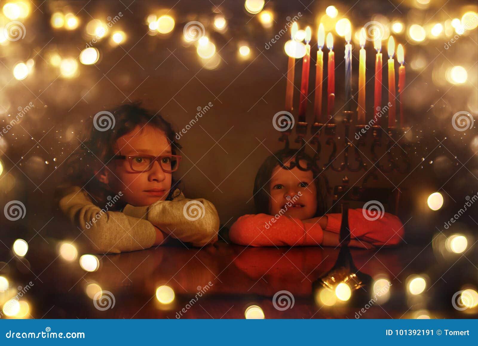 Immagine scura del fondo ebreo di Chanukah di festa con due bambini svegli che esaminano i candelabri del menorah e la latta trad