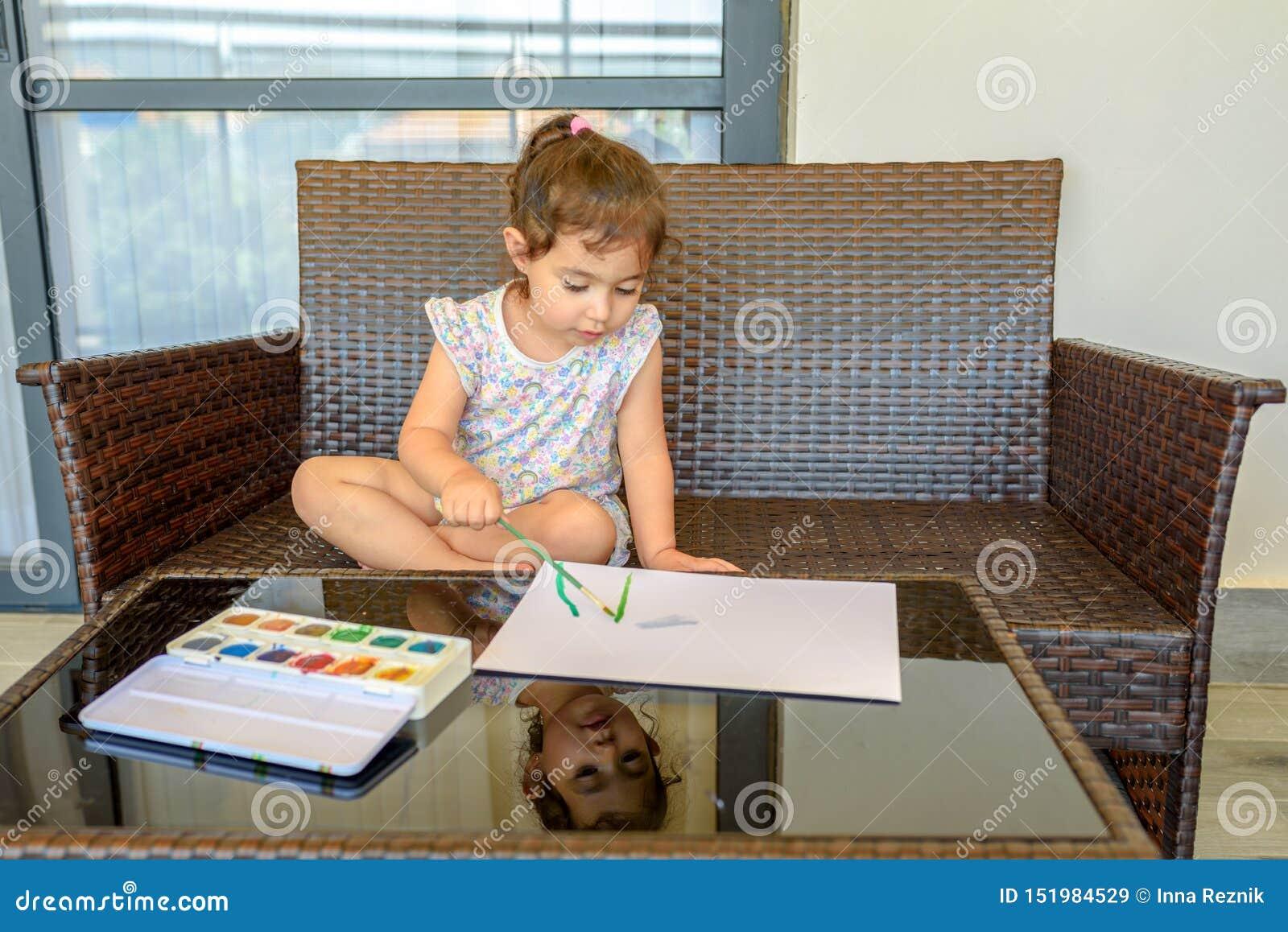 Immagine sveglia della pittura della bambina su fondo interno domestico Ragazzo e ragazze che si siedono sullo scrittorio pratica