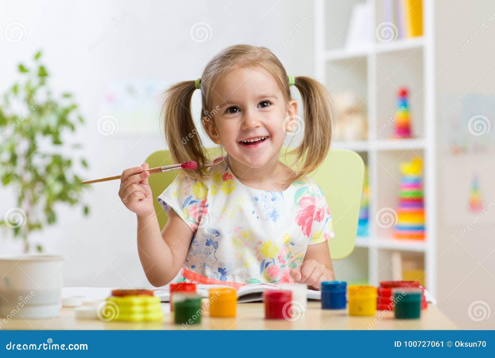 Immagine sveglia della pittura della ragazza del bambino su fondo interno domestico