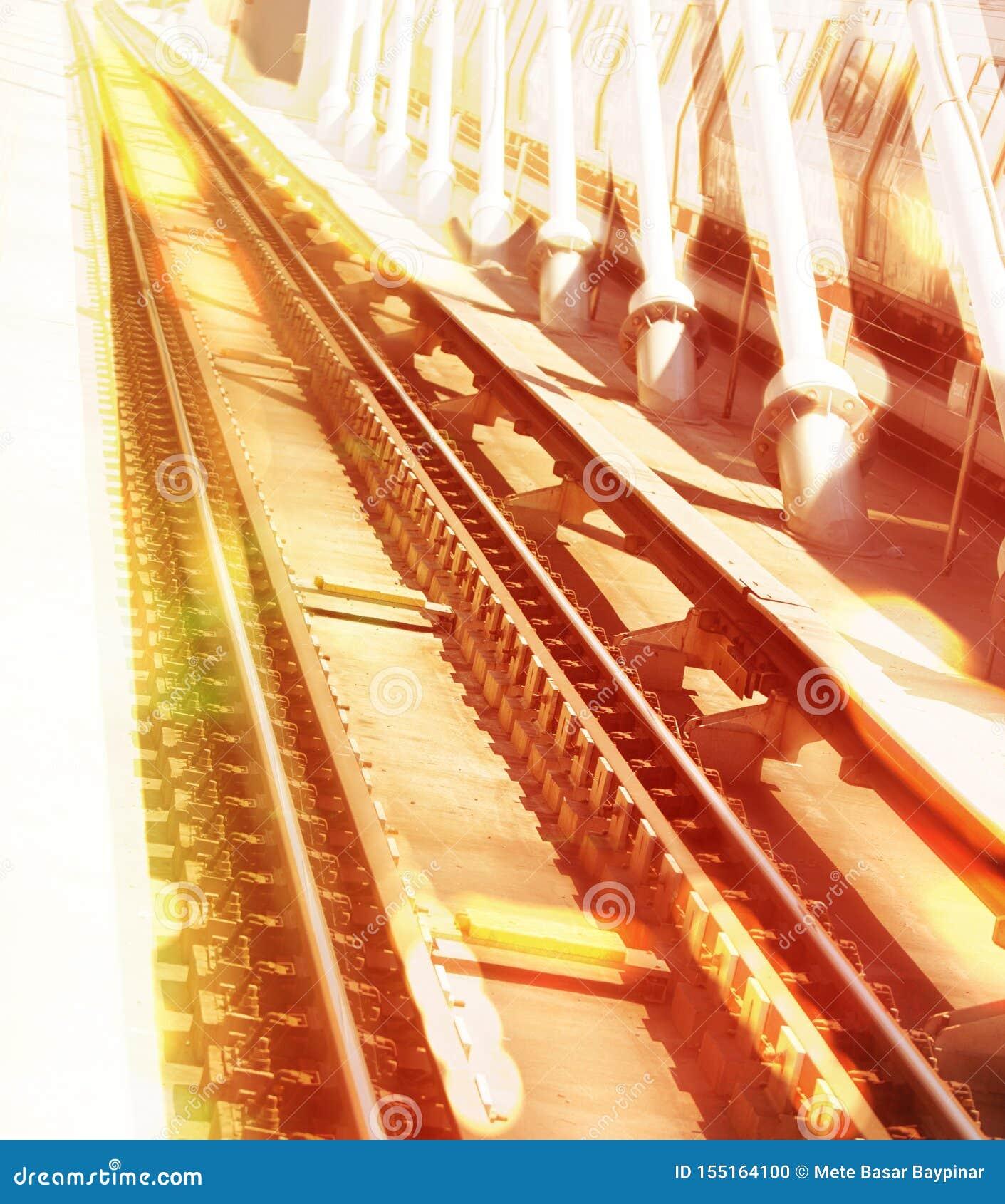 Immagine unica di prospettiva delle rotaie della metropolitana e delle bretelle brucianti di un ponte in uno sguardo vertiginoso
