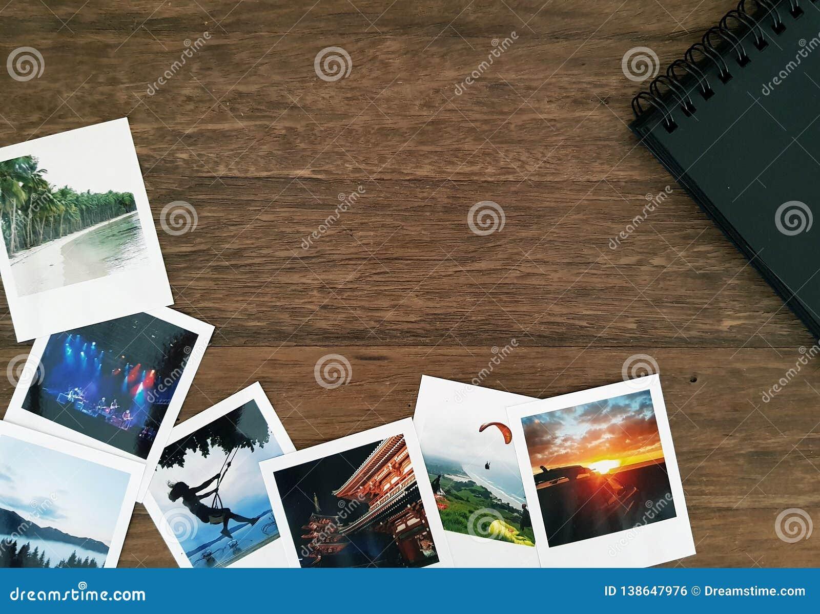 Immagini della polaroid e un album di foto a spirale nero su una tavola di legno con spazio bianco