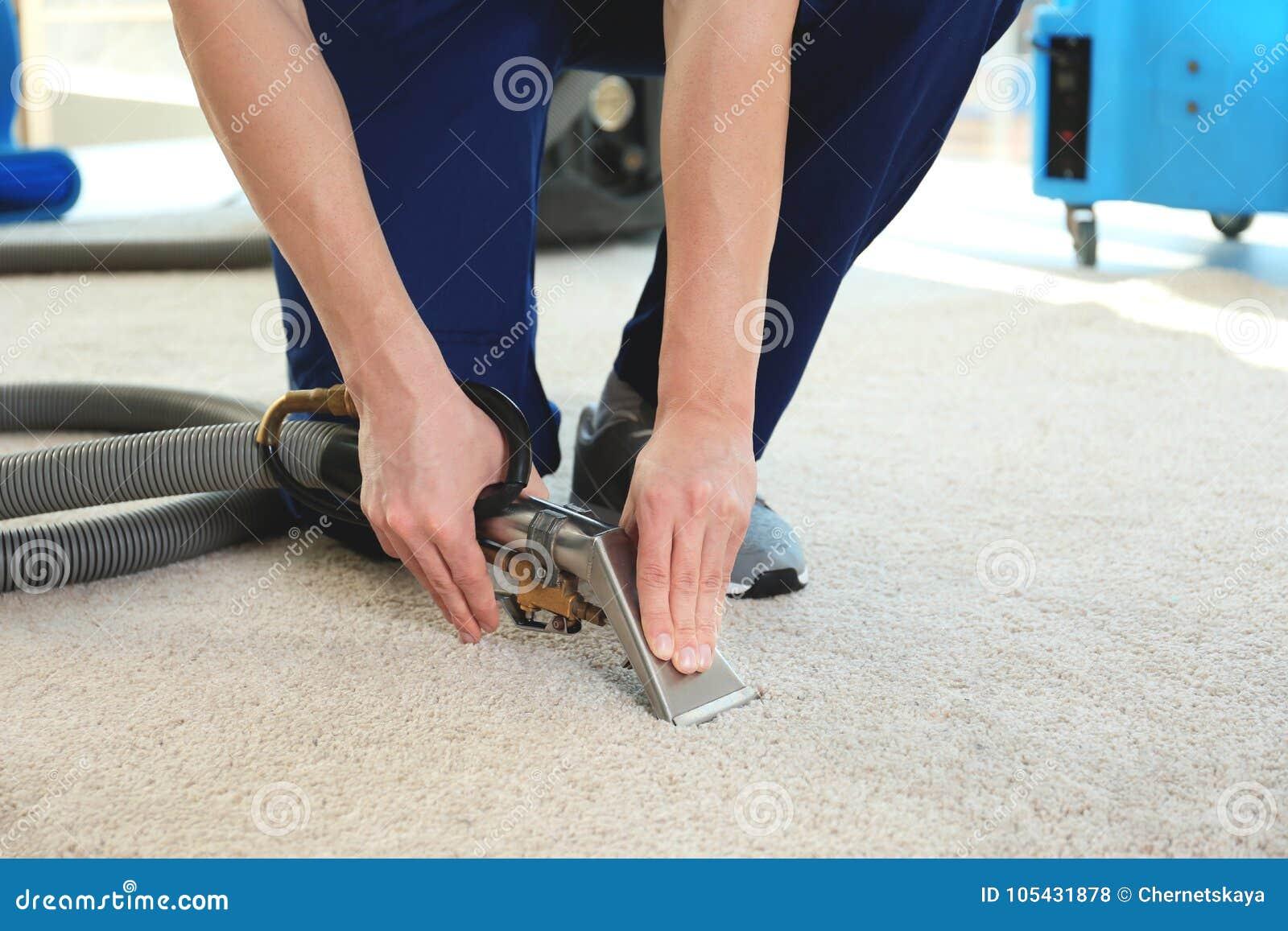 Impiegato del ` s della lavanderia a secco che rimuove sporcizia dal tappeto in piano
