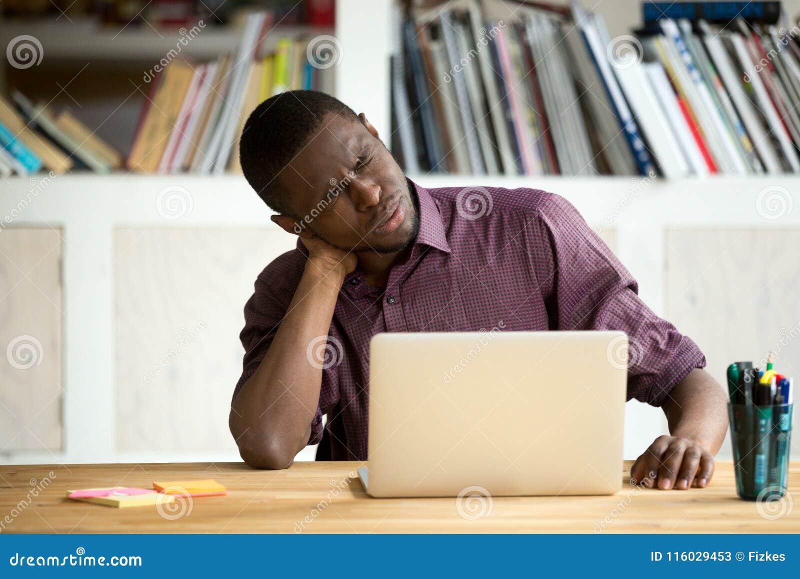 Impiegato di concetto afroamericano stanco che soffre dal dolore al collo