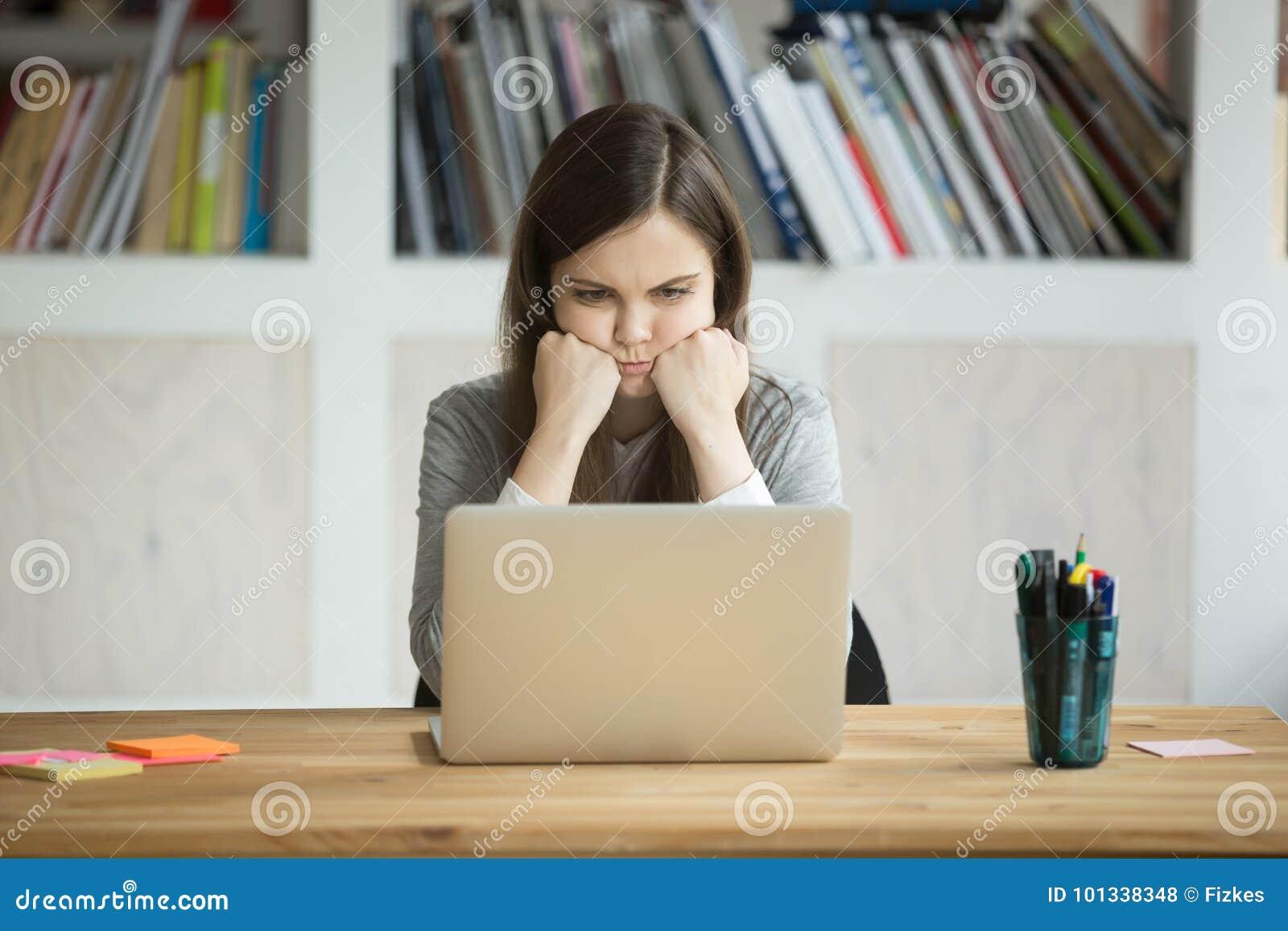 Impiegato di concetto divertente scontroso che esamina lo schermo del computer portatile