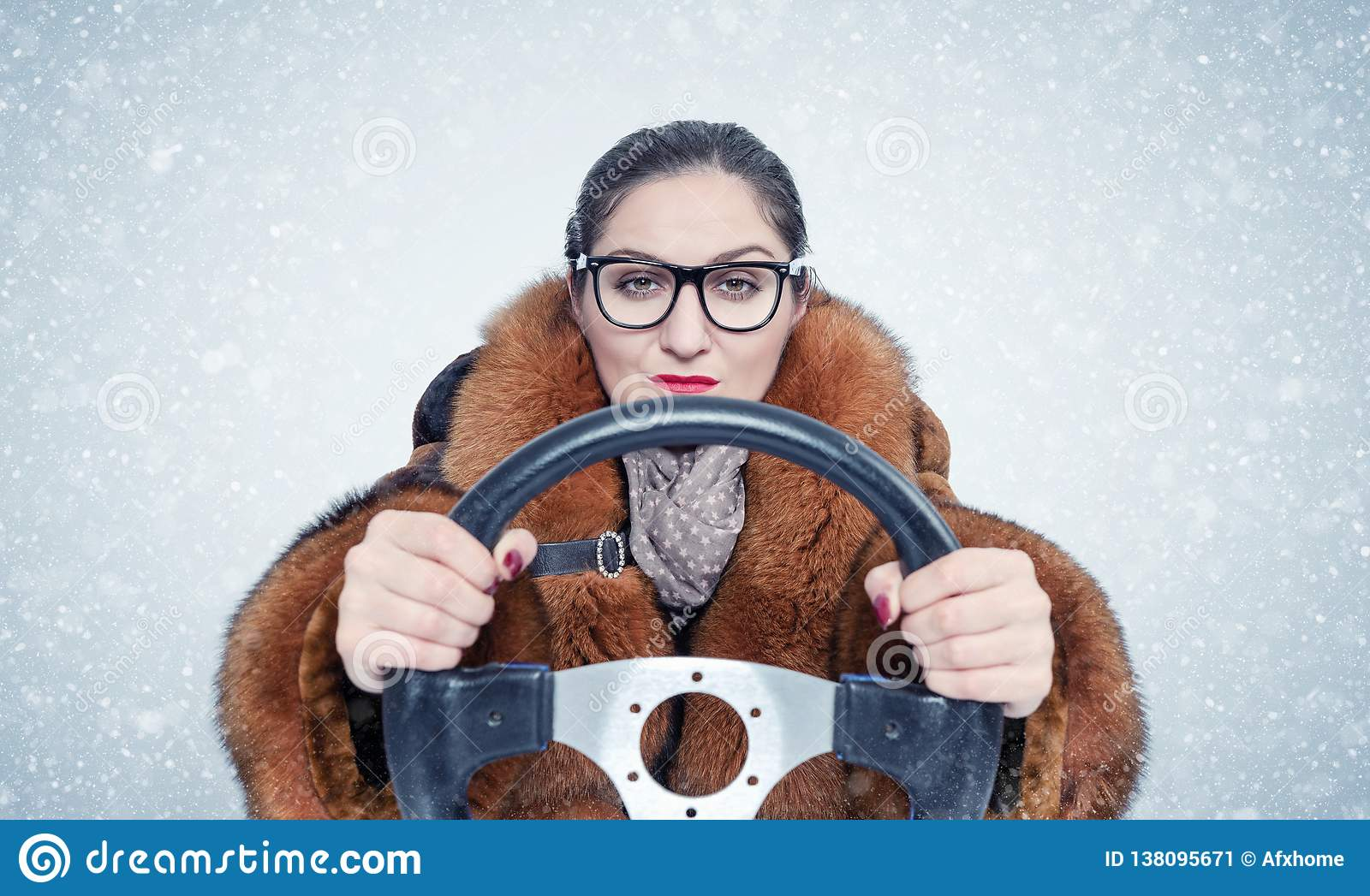 Important woman in glasses and a fur coat driving a car in the snow. On blue background.