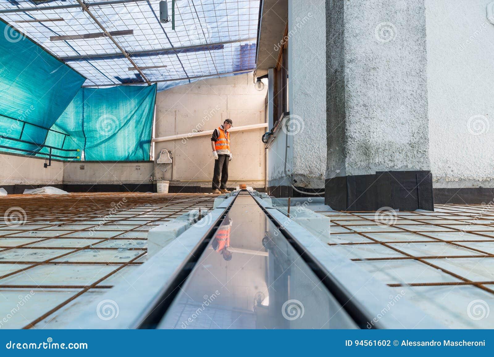 Imprägnierung und Wärmedämmung einer Terrasse - Dach Eine Berufsarbeitskraft installiert einen Abflusssinkkasten für Entwässerung