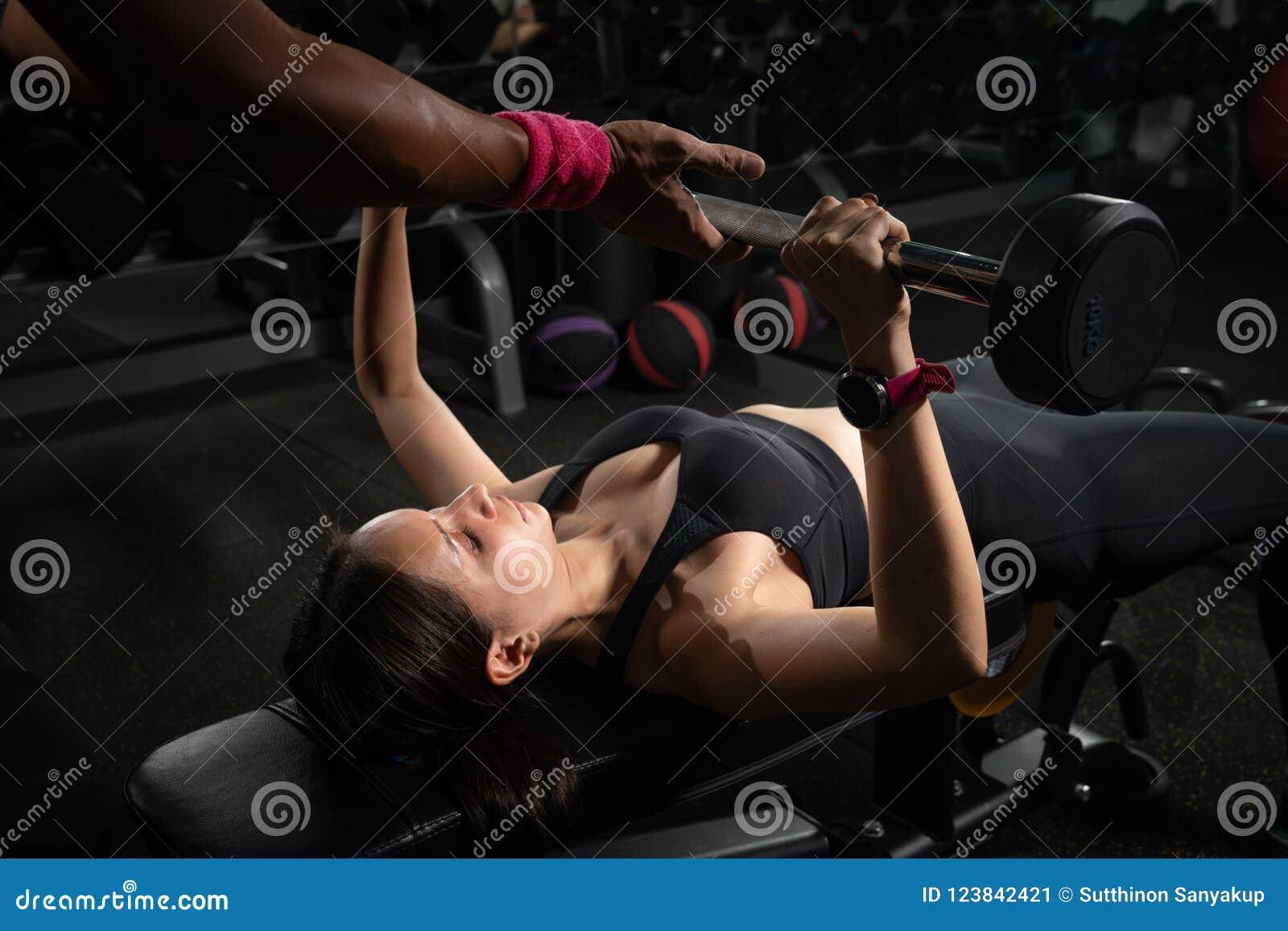 Imprensa de banco de ajuda da mulher do instrutor pessoal no gym, treinando com barbell