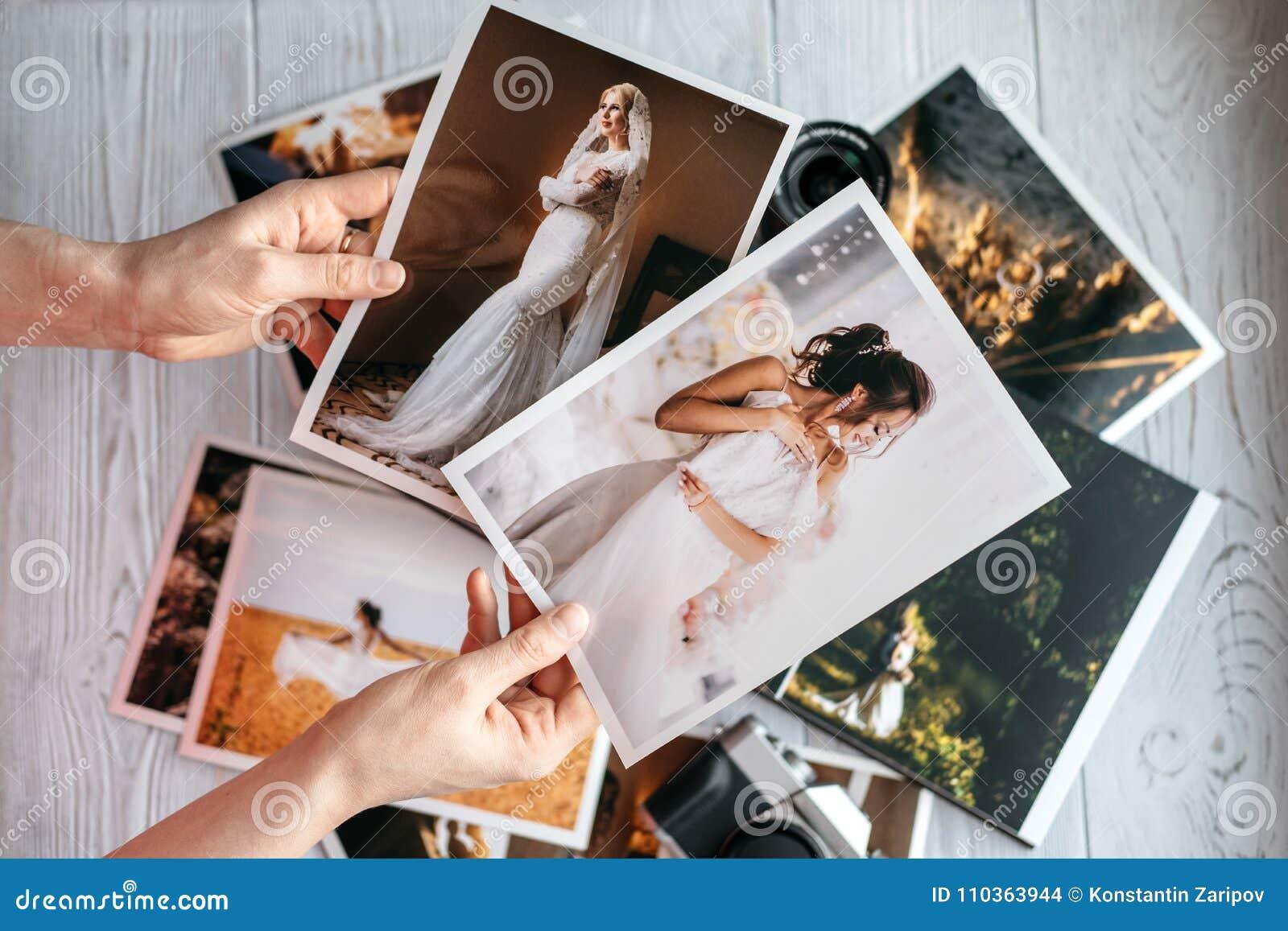 Impreso casandose fotos con la novia y el novio, una cámara del negro del vintage y las manos de la mujer con dos fotos