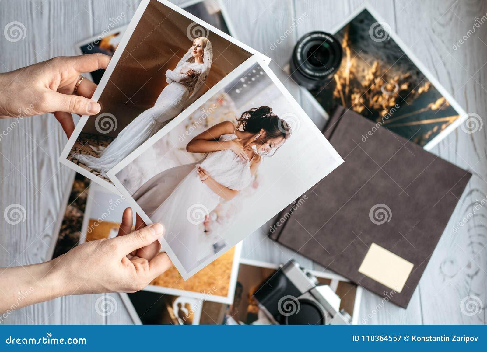 Impreso casandose fotos con la novia y el novio, una cámara del negro del vintage, photoalbum y las manos de la mujer con dos fot