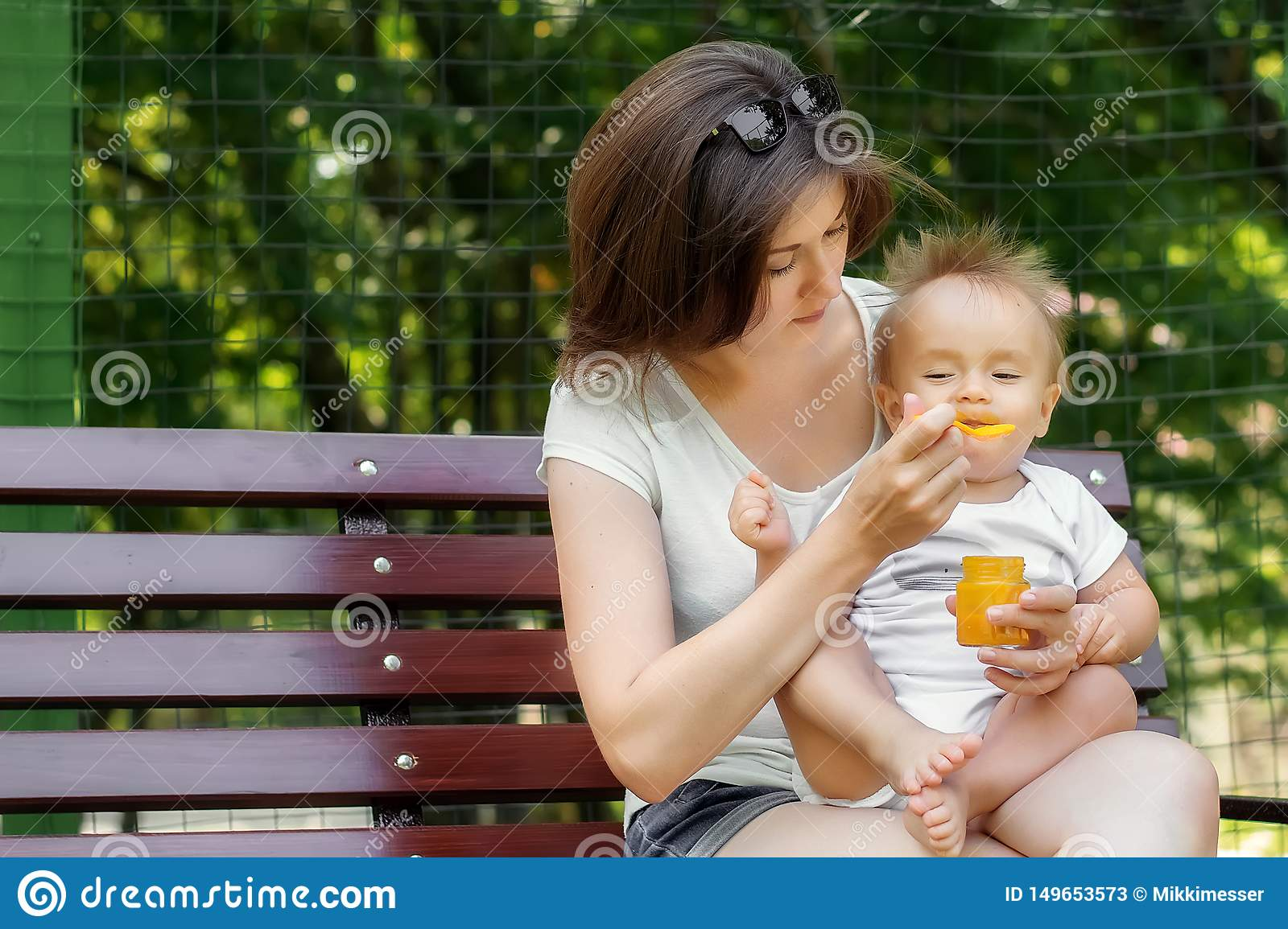 Improvised picnic with a baby: mother gives complementary feeding pumpkin puree to her hungry infant child sitting on bench