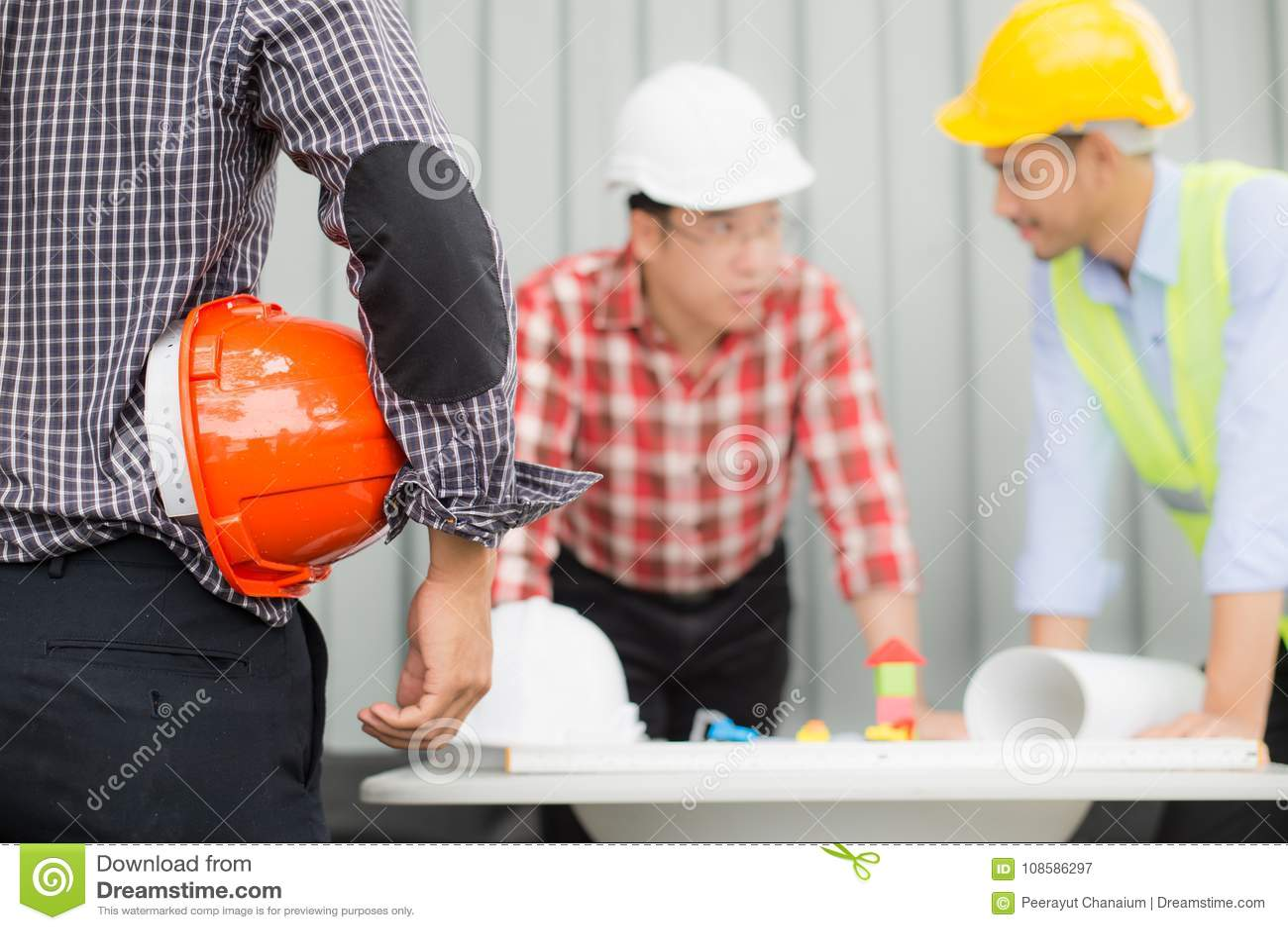 Inżynier i budowy drużyna jest ubranym zbawczego hełm i przyglądającego projekt na stole