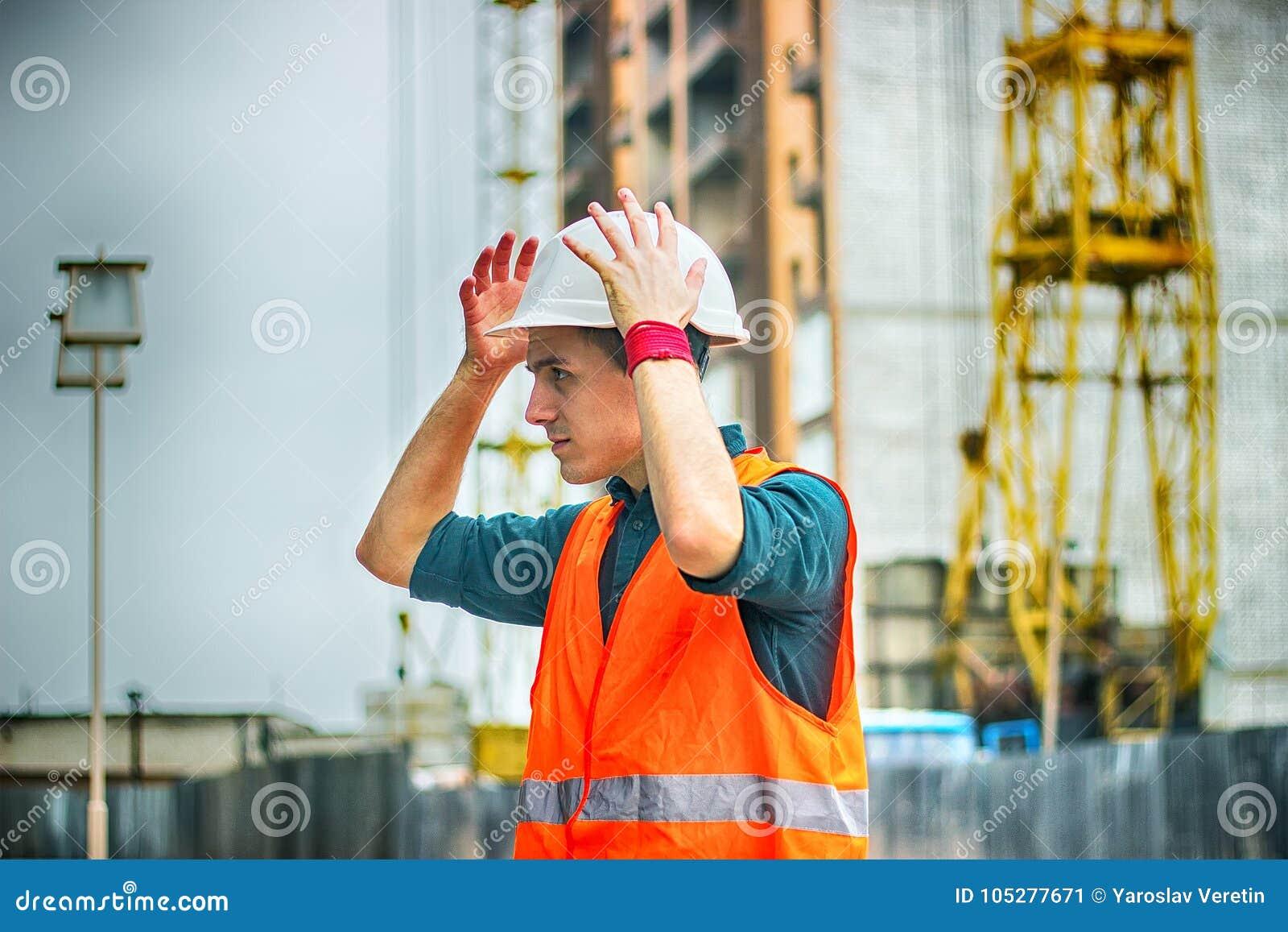 Inżynier lub architekt sprawdza osobistego ochronnego wyposażenia zbawczego hełm przy budową