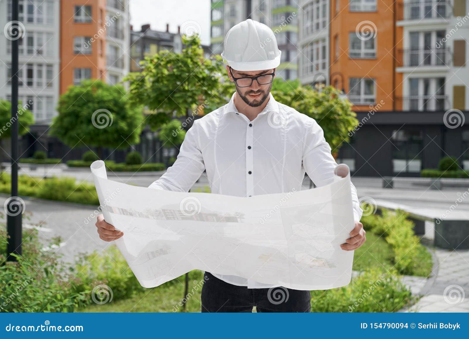 Inżynier trzyma architektonicznego projekt na papierze w hardhat