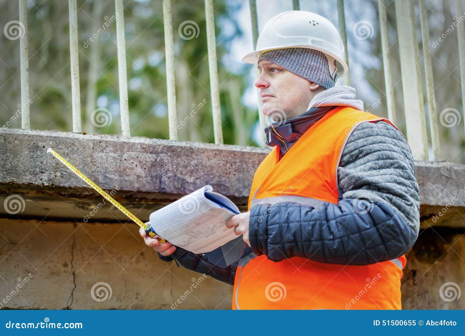 Inżynier z taśmy miarą i dokumentacja pod mostem