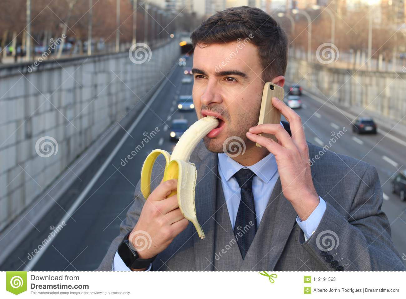 Inappropriate man biting a banana while calling