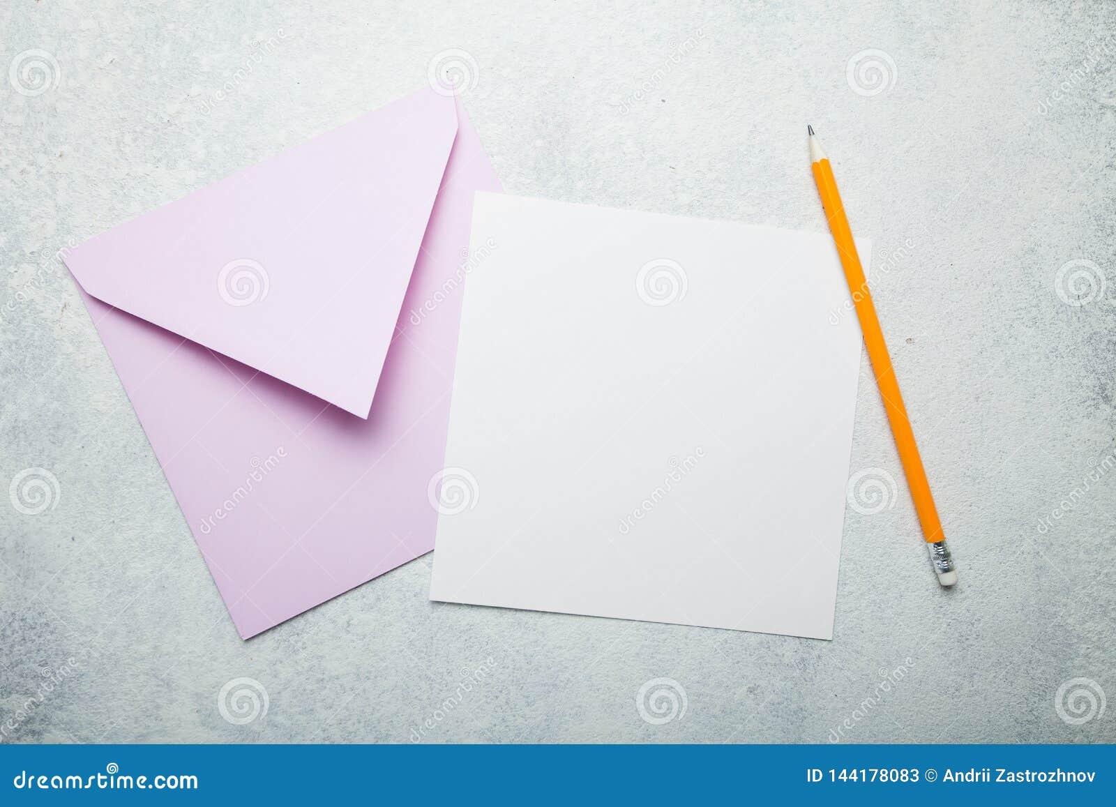 Inbjudanbokstav eller vykort Ett tomt fyrkantigt stycke av papper med utrymme för text, ett rosa kuvert och en blyertspenna på en