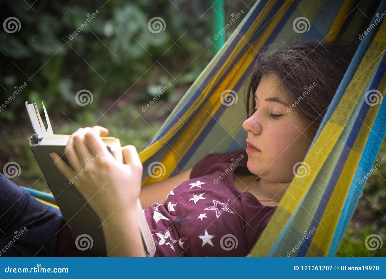 Inbunden tonåringflickaläsebok i hängmatta