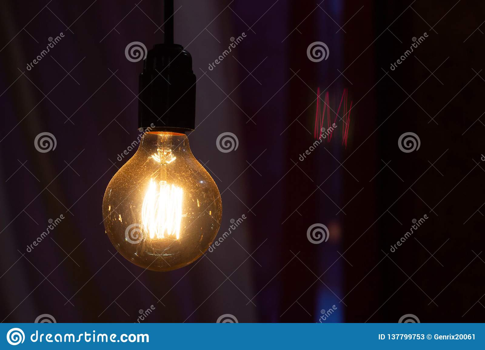 Incandescent bulb hanging in a night restaurant, copy space