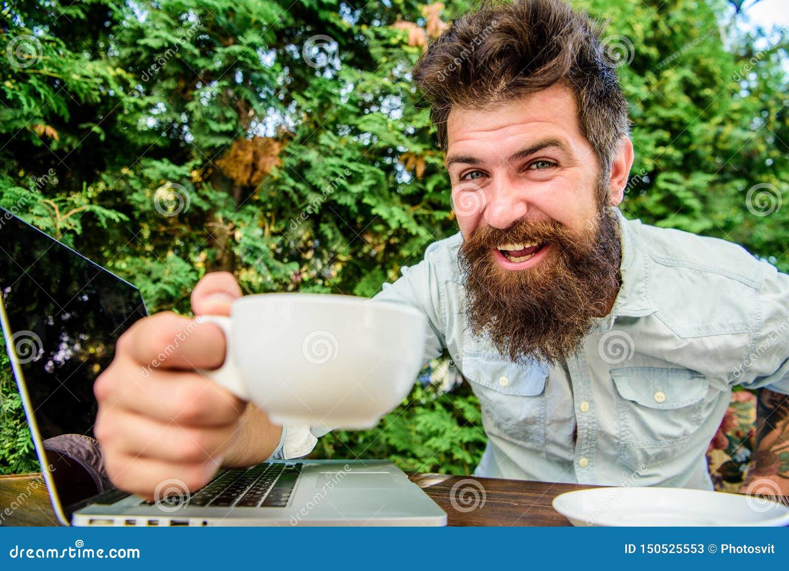 Inconformista barbudo brutal en el descanso para tomar caf? Hombre feliz con la computadora port?til Negocio ?gil ?xito de asunto