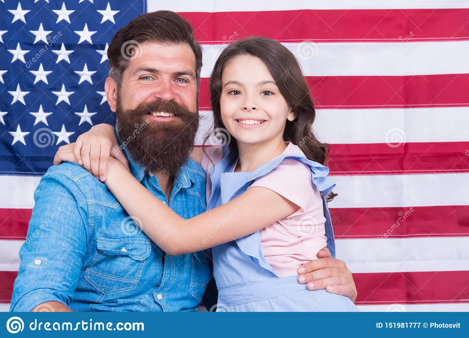 Inconformista barbudo del americano del padre y pequeña hija linda con la bandera de los E.E.U.U. El derecho fundamental de la li