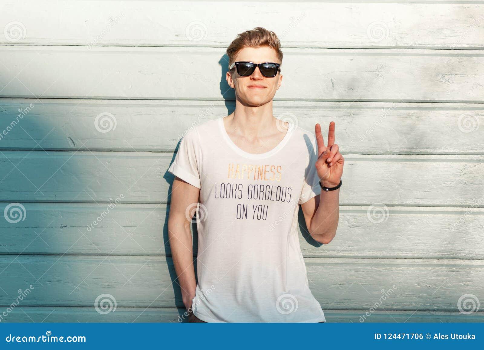c04e5c73bbbd3 El inconformista feliz joven hermoso del hombre con una sonrisa con las  gafas de sol de moda muestra un signo de la paz cerca de una pared azul de  madera en ...