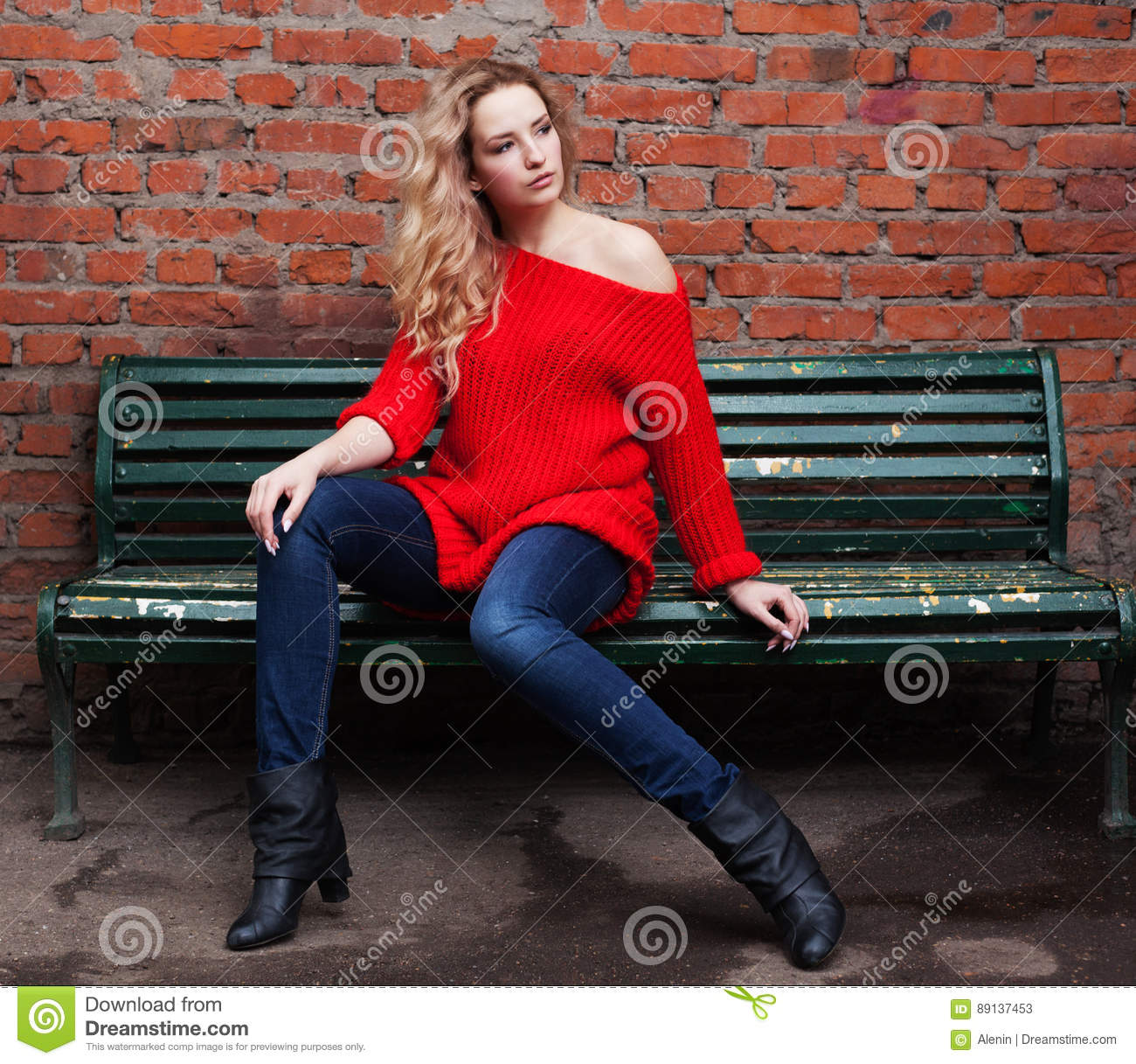 An Incredible Blonde Girl Posing In A Trendy Red Sweater, Jeans ...