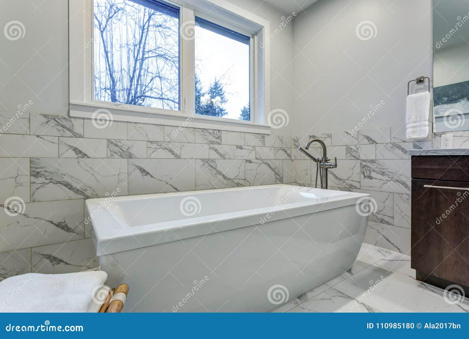 Incredible Master Bathroom With Carrara Marble Tile Surround Stock