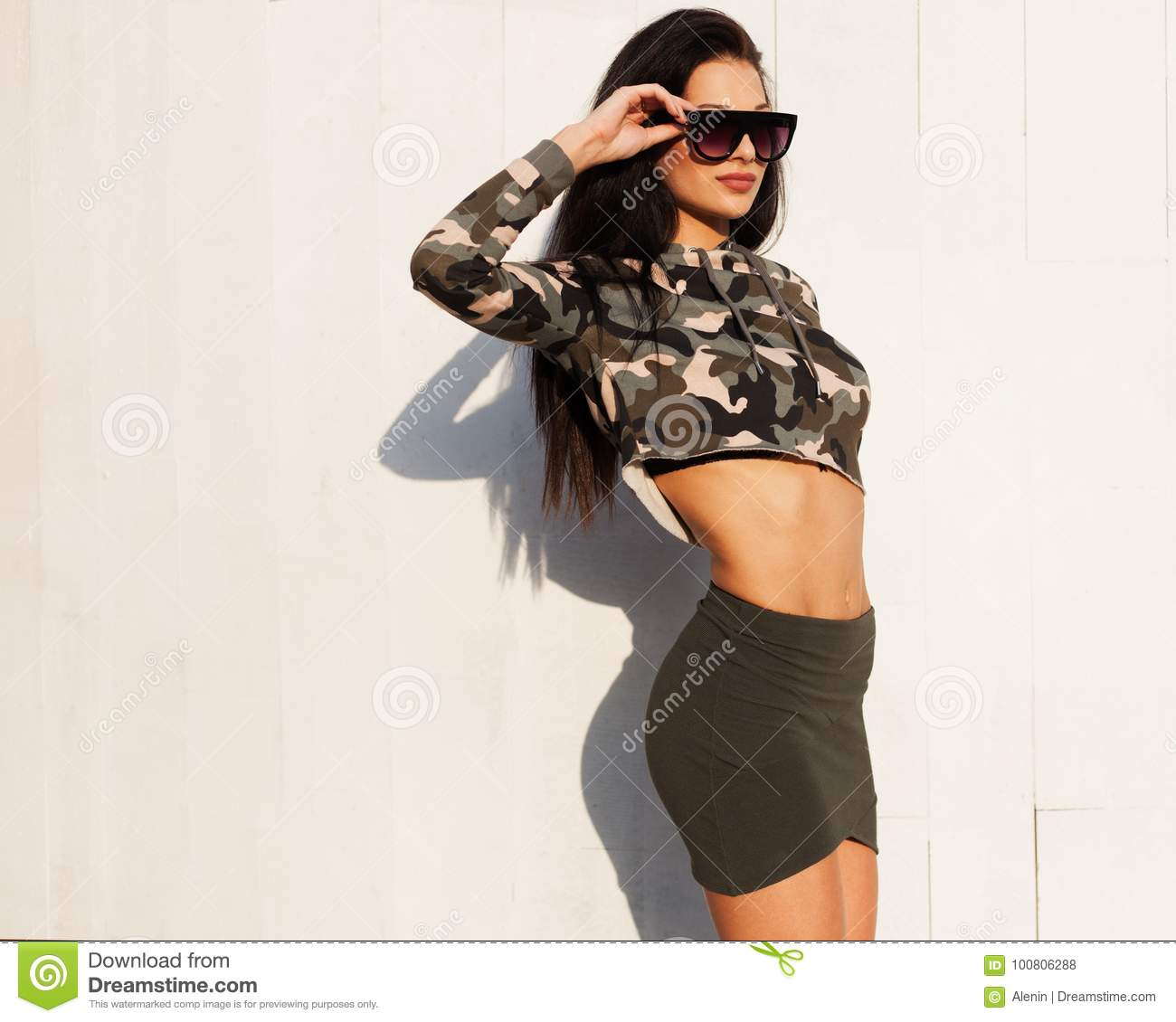 d96b2c129e1cb Incredible brunette girl in a short skirt and khaki trending camouflage  outfit posing in a white