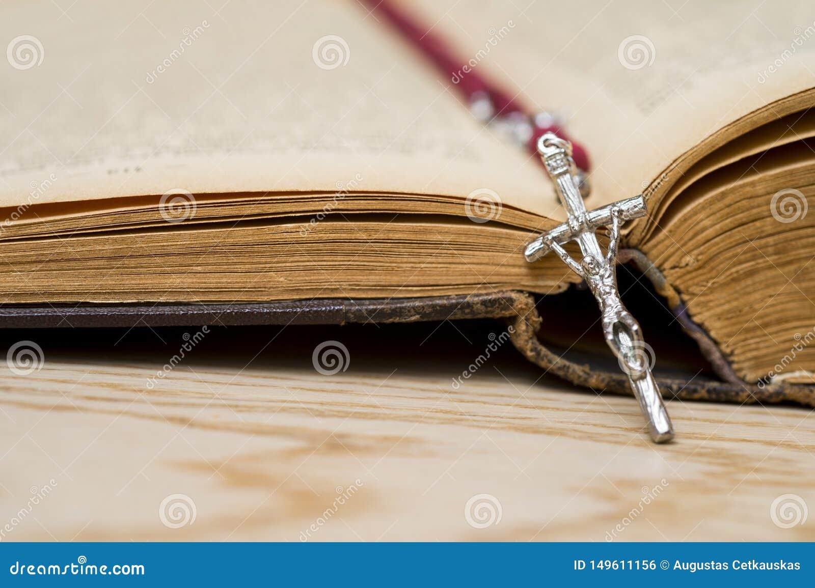 Incrocio sulla bibbia su un fondo di legno Libro sacro