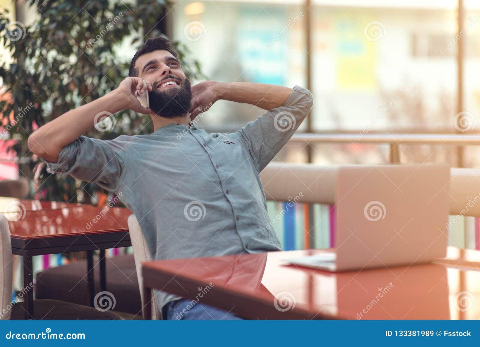 Indépendant barbu heureux enthousiaste lisant l email avec des résultats au sujet de victoire dans le concours en ligne moderne s