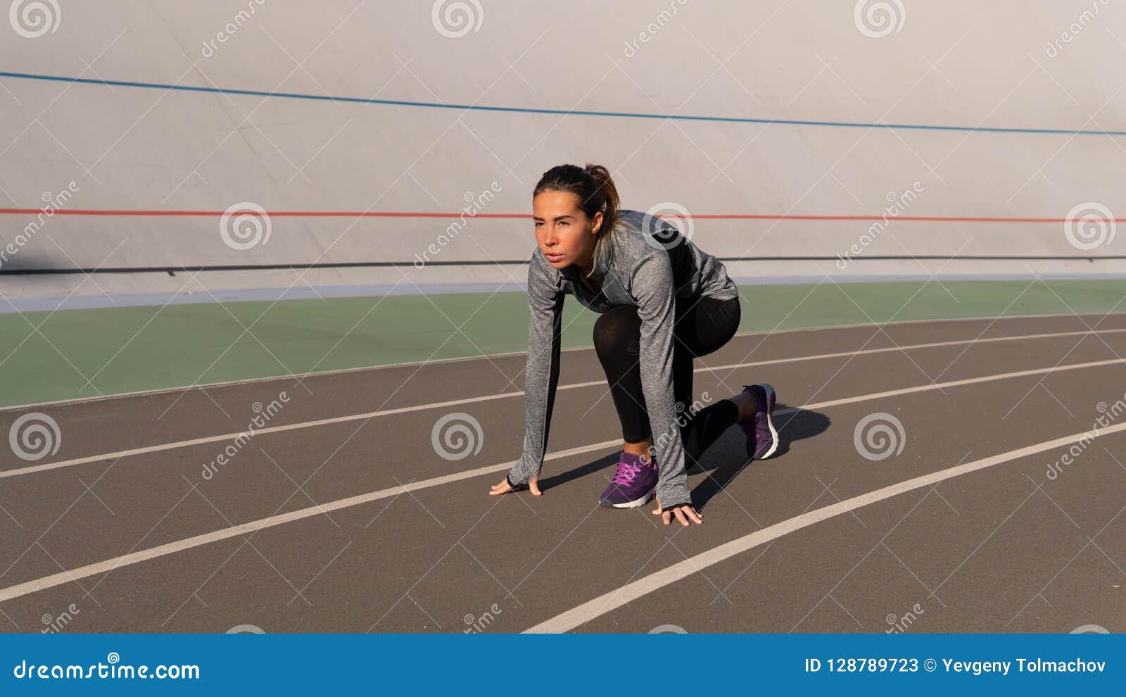 Independed-Brunettefrau, die für den Lauf auf der Läuferbahn sich vorbereitet