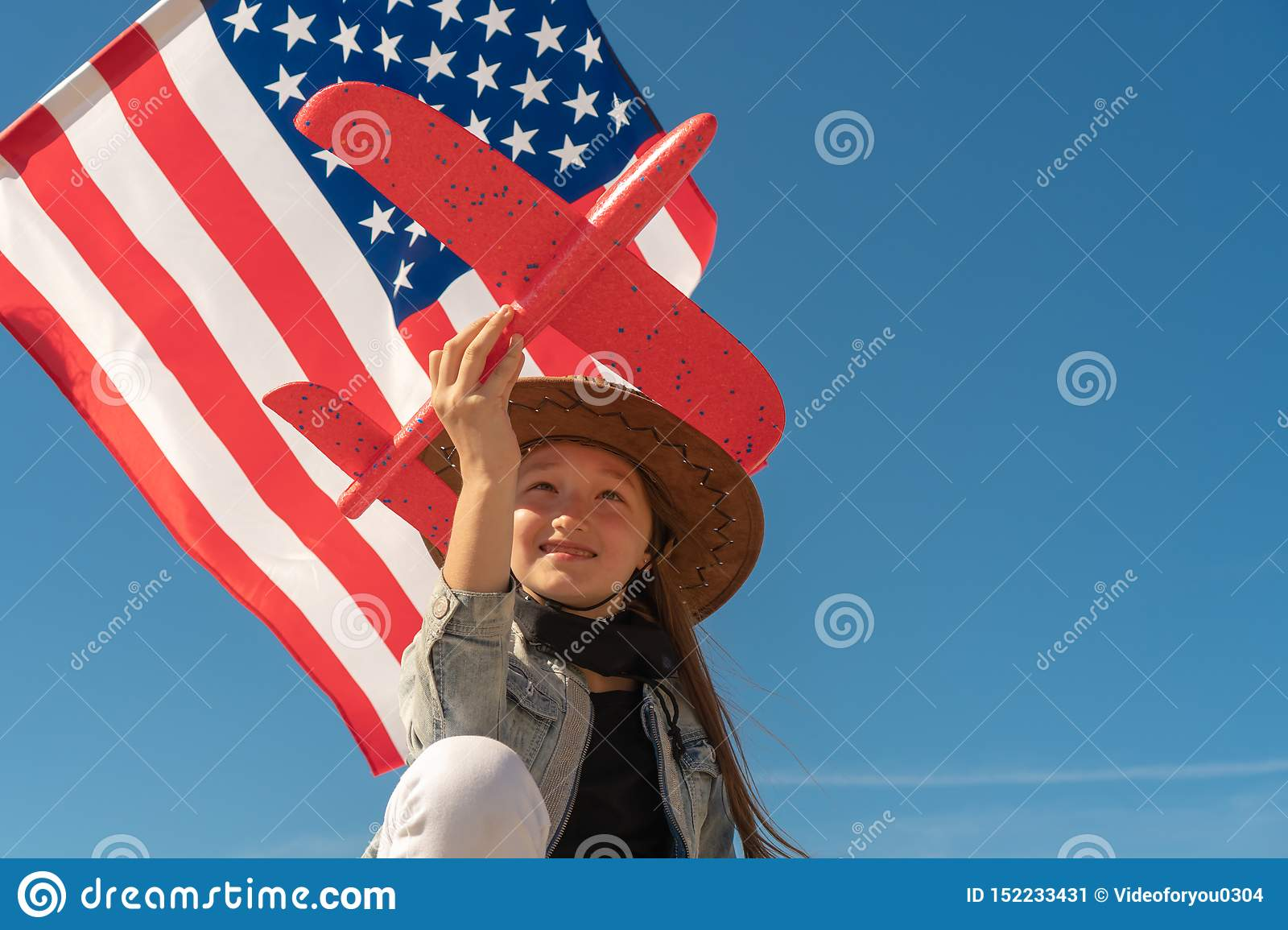 Independence Day.Beautiful girl in a cowboy hat on the background of the American flag is holding a red plane. USA celebrate 4th