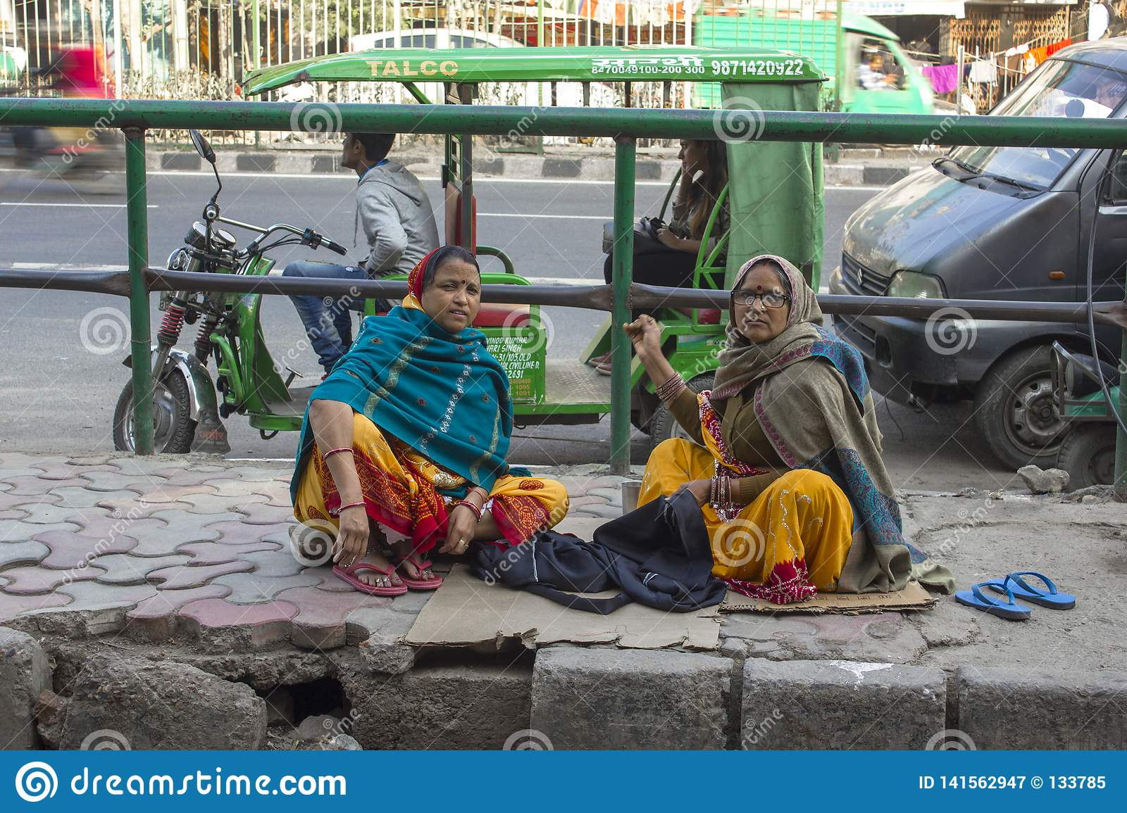 Indian adult women sew clothes sitting on the sidewalk against the backdrop of urban traffic