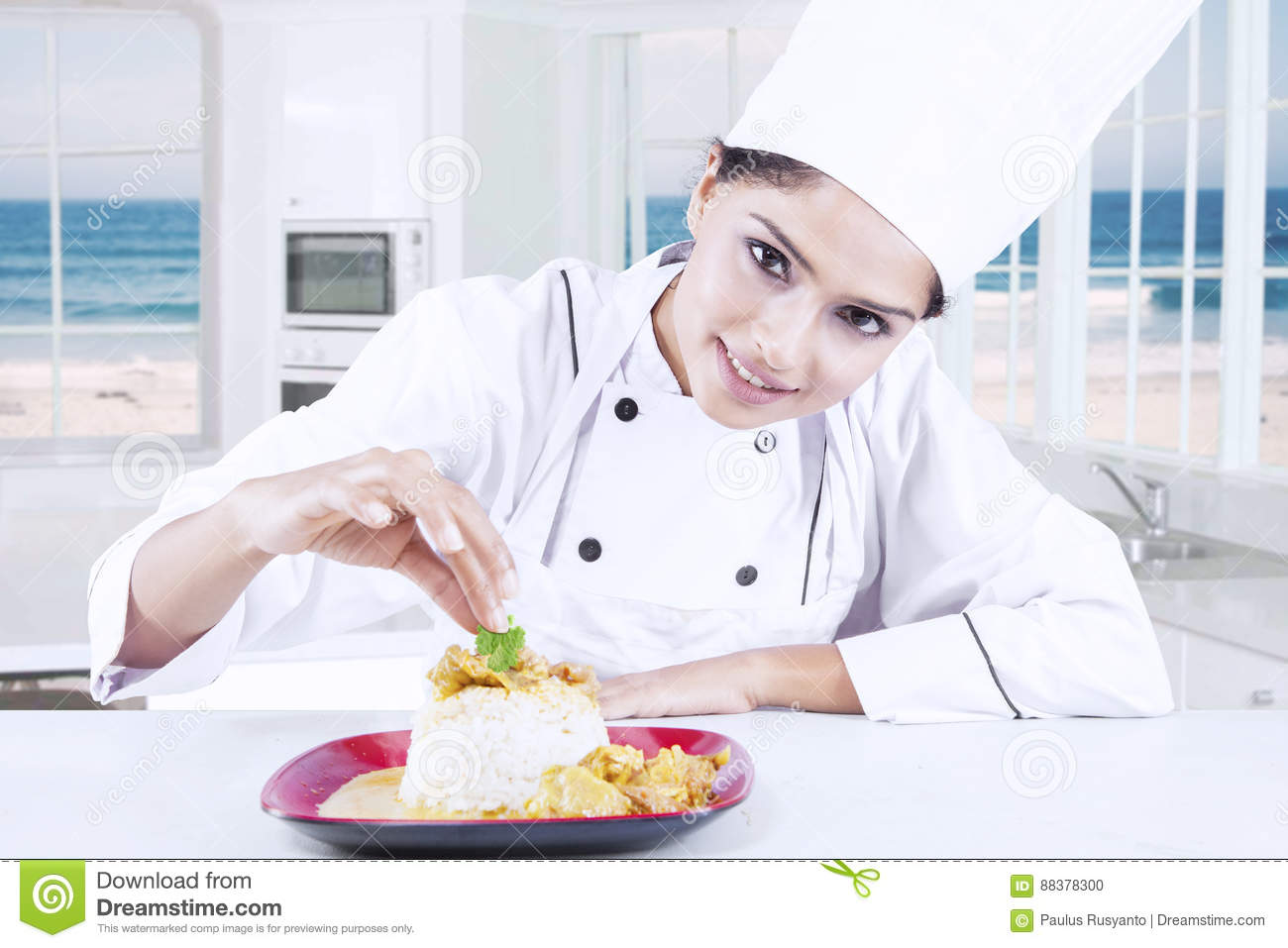Indian Chef Decorating Food In The Kitchen Stock Photo