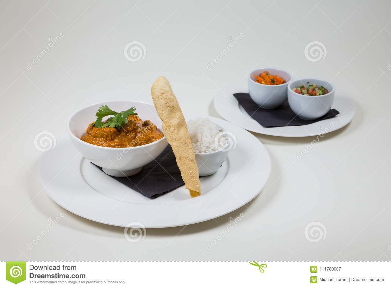 Indian Curry in a white bowl with rice on a white plate on a white background isolated