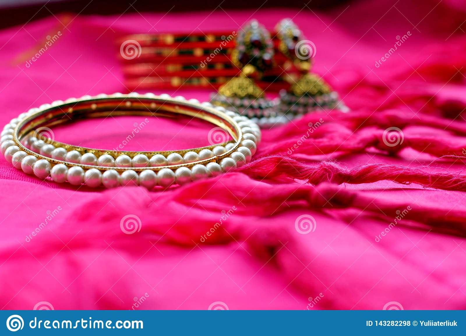 Indian ethnic jewelry bracelets and earrings on pink fabric