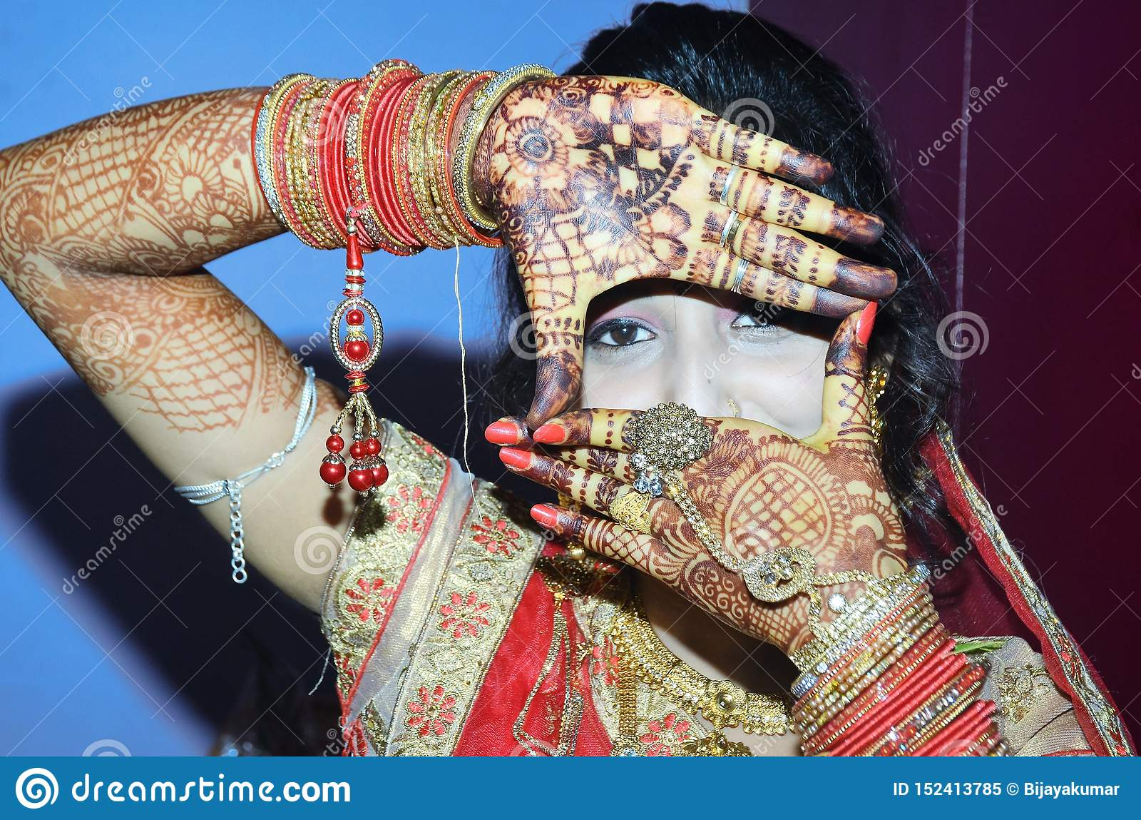 An Indian groom showing her eyes from her hand design