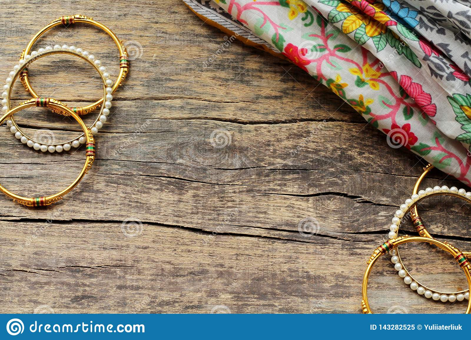 Indian jewelry bracelets and floral ethnic fabric lie on a wooden background