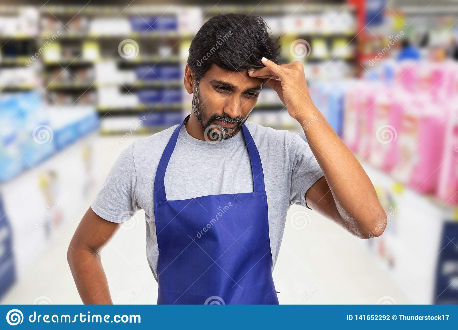 Hypermarket worker touching forehead as stress concept