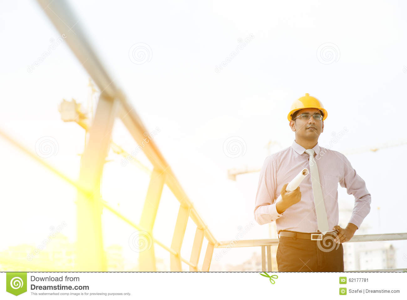 4ad0d7db8c1 Portrait of Asian Indian male site contractor engineer with hard hat  holding blue print paper at construction site