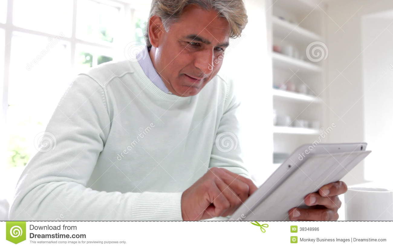 Indian Man Using Digital Tablet In Kitchen At Home  Mature, forties